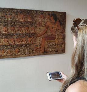 Bild på person vid konstverk med konstverket i mobilen